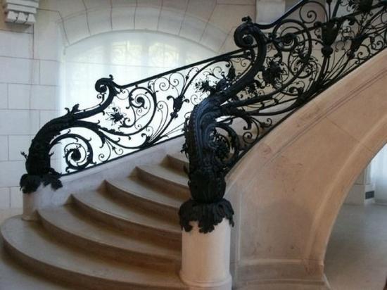 Каменная винтовая лестница с коваными поручнями и массивными балясинами